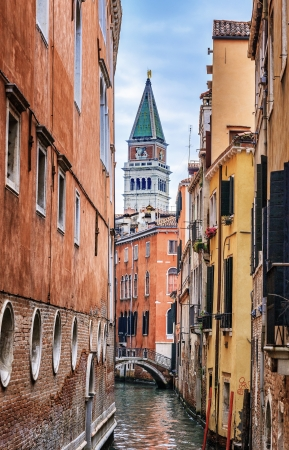 Narrow canal in Venice and st. Marcus bell tower in background