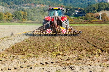 plough land: Ploughing heavy tractor during cultivation agriculture works at field with plough  Stock Photo