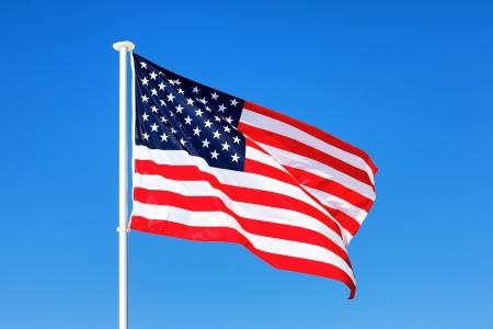 アメリカの国旗が青空に手を振っています。 写真素材