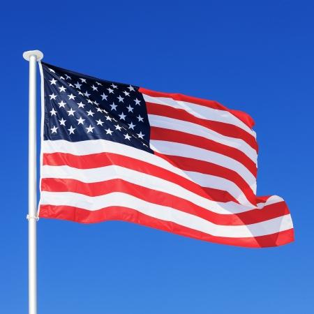 american flag waving: The American flag waving in blue sky
