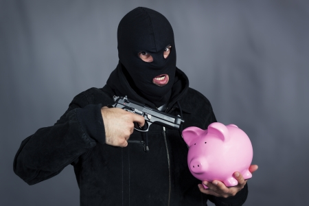 Man with gun on ping piggy bank photo
