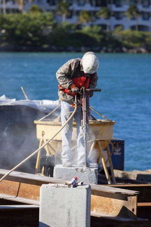 mounter: Man working with jackhammer in a harbor Stock Photo