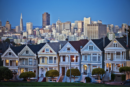 The Painted Ladies of San Francisco, California sit glowing amid the backdrop of a sunset and skyscrapers.  版權商用圖片