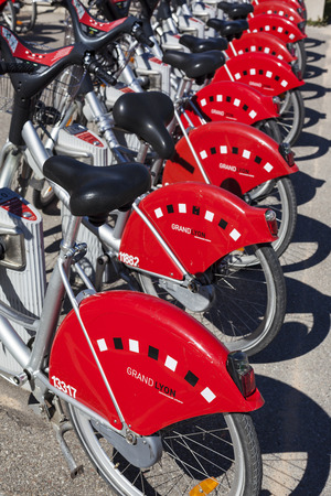 v cycle: LYON, FRANCE - AUGUST 2014 - Shared bikes are lined up in the streets of Lyons, France. Velov Grand Lyon, launched in May 2005, has over 340 stations and 3000 bikes throughout the Grand Lyon area.
