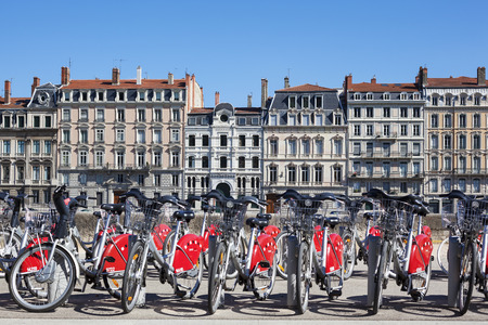 v cycle: LYON, FRANCE - AUGUST 2014 - Shared bikes are lined up in the streets of Lyon, France. Velov Grand Lyon, launched in May 2005, has over 340 stations and 3000 bikes throughout the Grand Lyon area.  Editorial