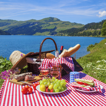 Picnic in alpine mountains with lake on background photo