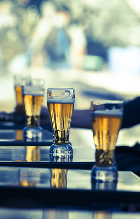 un bottled: glasses of beer on a table in a restaurant  Stock Photo