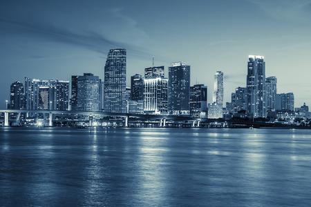 マイアミのスカイライン パノラマ都市の高層ビルと反射で海に架かる橋の夕暮れ時に