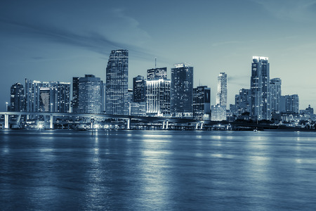 Miami skyline panorama at dusk with urban skyscrapers and bridge over sea with reflection