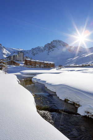 sunny day: View of Tignes village with sun and creek, France. Stock Photo