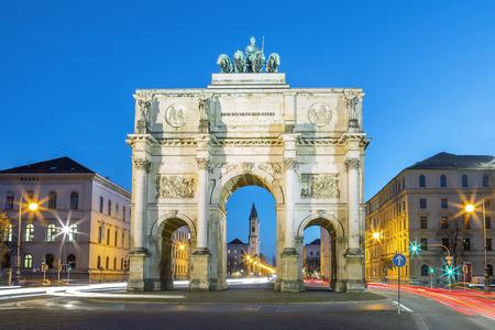 뮌헨의 Siegestor (영어 : Victory Arch). 이것은 아치 주위를 돌아 다니는 교통과 함께 황혼에 긴 노출입니다 스톡 콘텐츠
