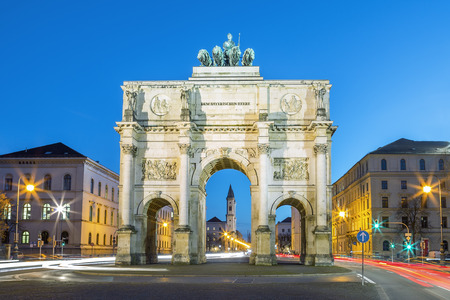 The Siegestor (english: Victory Arch) in Munich. This is a long exposure at dusk with traffic going around the arch Stock Photo