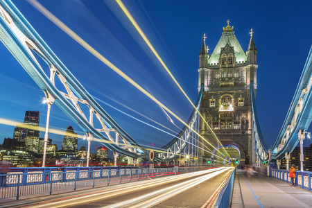light traces: Tower Bridge in London at night with moving red double-decker bus leaving light traces