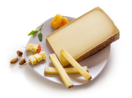 queso: Queso gruyere suizo en un plato sobre fondo blanco Foto de archivo