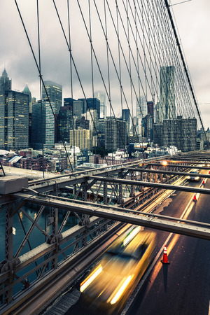taxi famous building: Taxi cab crossing the Brooklyn Bridge in New York, Manhattan skyline in background Stock Photo