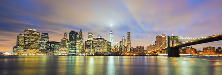 Panoramic view of New York City Manhattan midtown at dusk with skyscrapers illuminated over east river