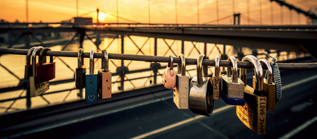 new love: NEW YORK - JULY 11, 2015: Love locks on the Brooklyn Bridge, New York, with sunrise in the background. Editorial