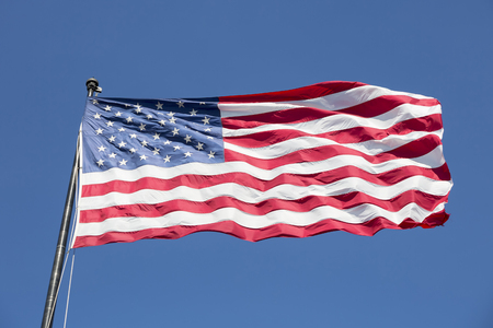 red flag up: American flag on the blue sky, USA. Stock Photo