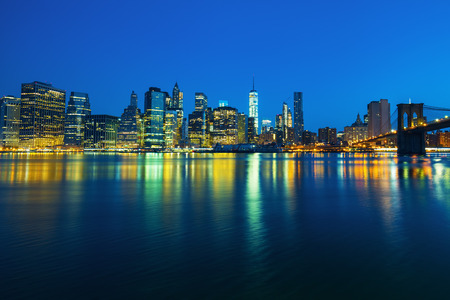 new york city panorama: New York City Manhattan midtown at dusk with skyscrapers illuminated over east river