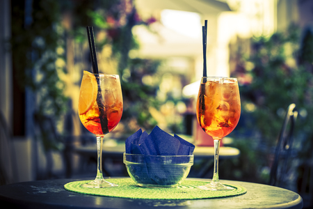 alcoholic beverage: Aperol Spritz Cocktail. Alcoholic beverage based on table with ice cubes and oranges.