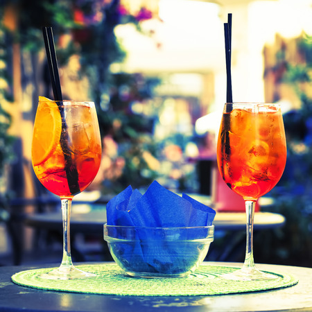 alcoholic beverage: Aperol Spritz Cocktail. Alcoholic beverage on table with ice cubes and oranges.