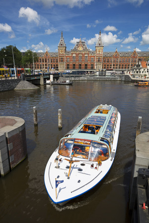 canal street: Amsterdam, Netherlands, JULY 6, 2016: canal cruise boat in front of amsterdam central railway station Editorial