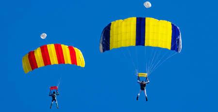 Two parachutists against a blue sky