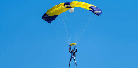 Parachutist with yellow and blue parachute against a blue sky