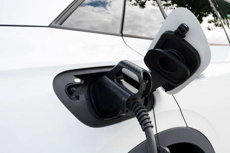 New white electric car charging at a station
