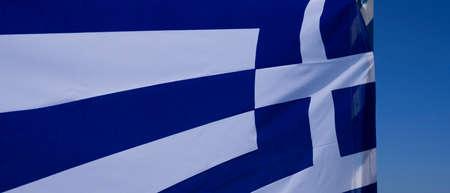 View of greek flag in the wind, Oia, Santorini, Greece 免版税图像