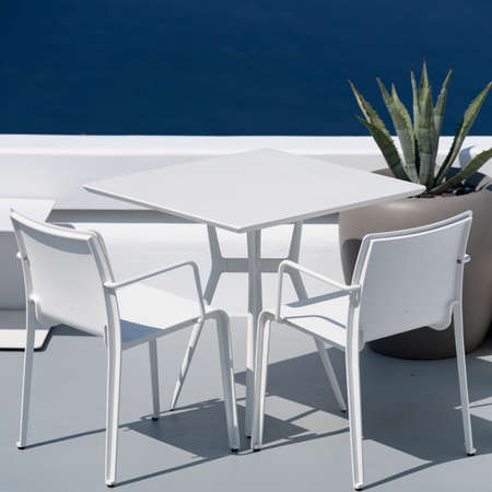 White table and chairs on terrace in Oia, Santorini. 免版税图像