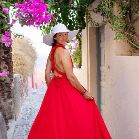 Red dressed woman in a street in Oia, Santorini, Greece