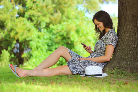 under tree: Young woman using her smart phone outdoors Stock Photo