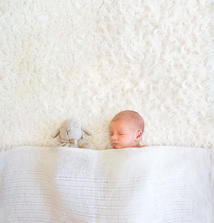 Een pasgeboren baby slaapt naast zijn schapen onder een zachte deken