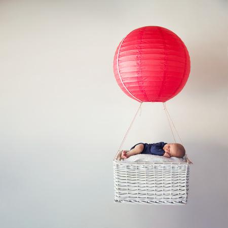 Neugeborenes Baby schläft in einem kleinen Korb mit einem Luftballon