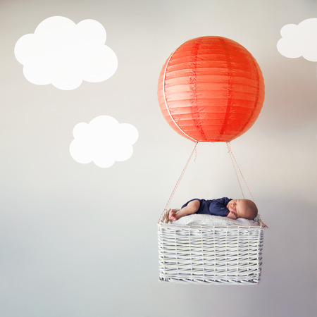 baskets: Tiny newborn baby flying among the clouds Stock Photo