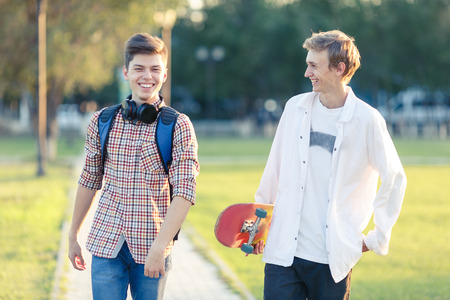 Two teenagers in a good mood with a skateboard rest in the park at sunset of the day