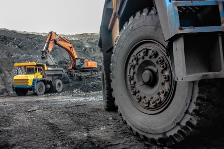 Working Environment: Excavator loading the iron ore into the heavy mining truck Stock Photo