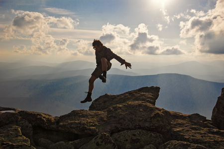 Hiker jumping over rocks with sunset sky on the background