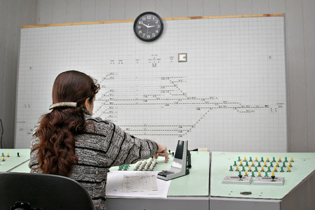 Young female dispatcher working. Train young woman manager working on the background information board