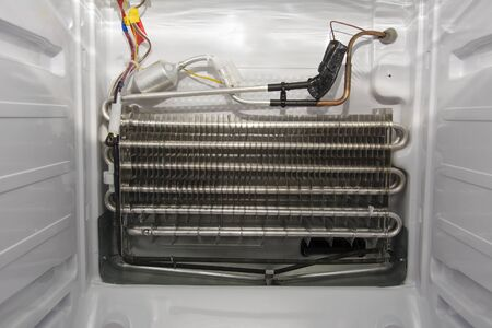 Disassembled white modern home freezer with stainless steel radiator, copper piping and sensor, inside view. Concept of maintenance and repair of refrigerators.