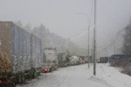 Cars on winter road traffic jam city. Winter weather on the city highway, the view from police car patrol through steamy glass window in the fog and snow road. Snowfall, ice, blured background, selective focus