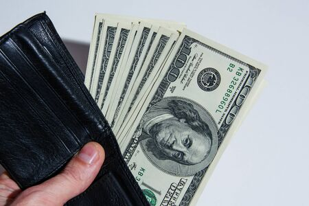 Happy young businessman holds a wallet in his hand with money. 100 dollar bills in a black leather wallet Stock Photo