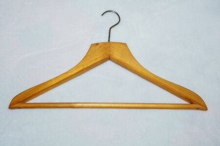 Wooden hanger for clothes with hook on white background.