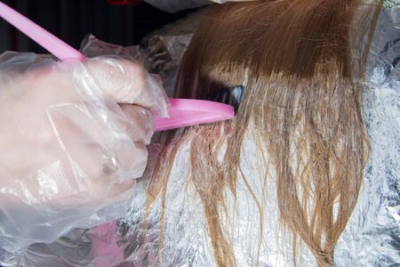 Hairdresser makeup artist hand in a transparent disposable glove applies hair dye with a pink brush on the hair of a blonde. Hair coloring process, highlighting.