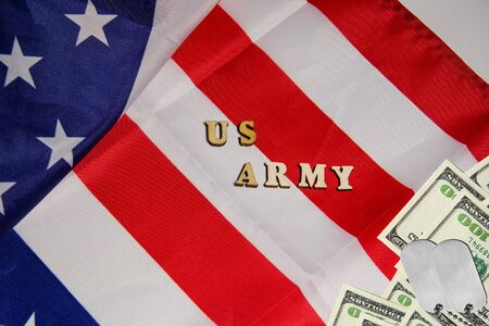 The soldier military tokens on dollar bills on the USA flag background with words US Army. Soldiers of fortune military power concept