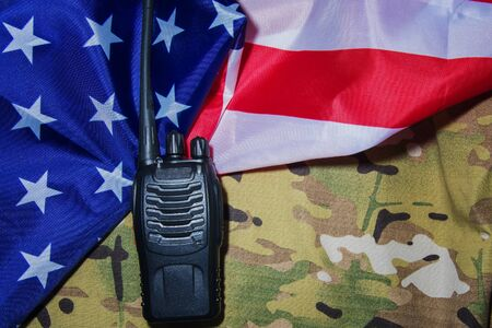 Portable black walkie-talkie on American flag and camouflage military background Фото со стока
