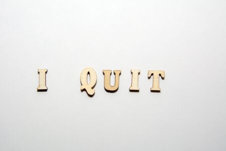 Inscription i quit isolated on white background from the wooden letters. Constructive dismissal concept