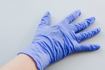 Human hand in blue latex glove, personal protective equipment medical accessory to ensure the safety of staff and patient. To protect the skin in contact with toxic substances, compliance with sterility.