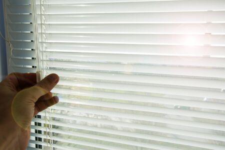 El hombre cierra o abre las persianas horizontales de aluminio blanco bajadas. A través de la ventana abierta entran los rayos del sol de primavera de la mañana. Foto de archivo